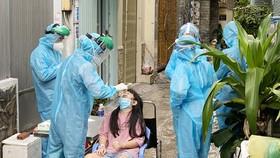 Nhân viên y tế lấy mẫu xét nghiệm SARS-CoV-2 cho người dân sống tại hẻm 415 Nguyễn Văn Công, phường 3, quận Gò Vấp, ngày 27-5-2021. Ảnh: CAO THĂNG