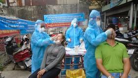 Nhân viên y tế lấy mẫu xét nghiệm cho người dân liên quan đến ca mắc Covid-19 ở chợ Bình Đông, quận 8