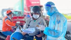 Kiểm tra giấy thông hành vào thành phố tại trạm Ngã 3 Làng - QL1A - Bình Chánh. Ảnh: HOÀNG HÙNG