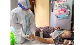 Nhân viên y tế chăm sóc cho bệnh nhân mắc Covid-19 tại nhà Ảnh: HOÀNG HÙNG