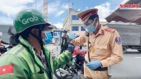 Lực lượng chức năng TPHCM kiểm tra giấy tờ một shipper. Ảnh: VĂN MINH