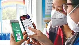 Chị Trần Thị Thanh Trang, huyện Bình Chánh, TPHCM hướng dẫn thành viên gia đình sử dụng app sổ sức khỏe điện tử trên nền điện thoại thông minh. Ảnh: HOÀNG HÙNG