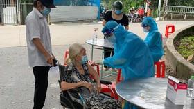 Nhân viên y tế tiêm vaccine cho người dân Ảnh:HCDC