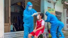 Nhân viên y tế lấy mẫu xét nghiệm cho trẻ em. Ảnh: HOÀNG HÙNG