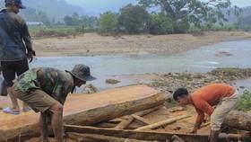 Hàng chục khối gỗ theo lũ đổ về chân cầu ở Quảng Ngãi