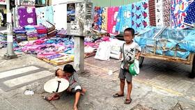 Trẻ em ăn xin trên đường phố, ở quận 5, TPHCM. Ảnh: TUẤN VŨ