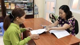 Luật sư Trần Ngọc Nữ (bên phải) hướng dẫn một phụ nữ bảo vệ quyền lợi của mình. Ảnh: HOÀNG LONG