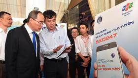 Bí thư Thành ủy TPHCM Nguyễn Thiện Nhân xem ứng dụng Sở Xây dựng trực tuyến SXD247, ra mắt tháng 12-2019 nhằm phục vụ tốt hơn nhu cầu của người dân về lĩnh vực xây dựng. Ảnh: VIỆT DŨNG