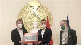 Chủ tịch Đảng Cộng sản Đức Patrik Köbele (trái) và ông Stefan Kühner (phải) trao số tiền quyên góp cho Đại sứ Nguyễn Minh Vũ. Ảnh: TTXVN