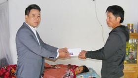 Thay mặt Báo SGGP, ông Nguyễn Bá Long, Bí thư Đảng ủy xã Đông Quang (Đông Sơn, Thanh Hóa) trao tiền của bạn đọc báo cho anh Lê Duy Thủy