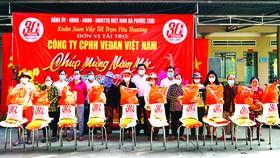 Đại diện công ty Vedan Việt nam (áo trắng giữa) cùng đại diện UBND xã Phước Thái, huyện Long thành, tỉnh Đồng Nai trao quà tết cho bà con tại địa phương