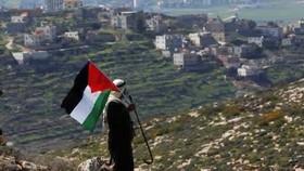 Một người đàn ông Palestine vẫy cờ Palestine trong cuộc biểu tình phản đối các khu định cư của Israel tại thành phố Nablus, Bờ Tây, hôm 26-2-2021. Ảnh: EPA