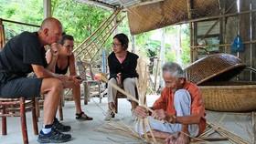 Ông Vũ Văn Khá (làng Kim Bồng, xã Cẩm Kim, TP Hội An) biểu diễn nghề đan thúng chai cho khách nước ngoài thưởng lãm