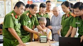 Cán bộ Đội Quản lý hành chính về trật tự xã hội Công an quận 12 làm thủ tục lấy vân tay cho em Phạm Minh Quân bị bệnh bại não tại cơ sở Mái ấm Minh Tâm