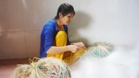 Chị Nguyễn Thị Bé Vinh dù bệnh tật vẫn gắng đan lưới kiếm tiền nuôi 2 con