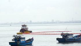 Các lực lượng cứu hộ cứu nạn triển khai các biện pháp chống tràn dầu trên biển sau khi va chạm giữa tàu chở dầu và cầu cảng tiếp dầu