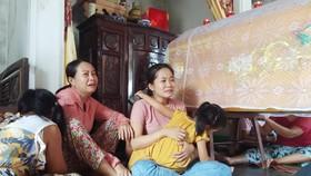 Chị Nguyễn Thị Ly và con gái ngồi thẩn thờ bên quan tài anh Khải