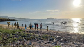 Lực lượng chức năng đưa thi thể hai thanh niên gặp nạn vào bờ.