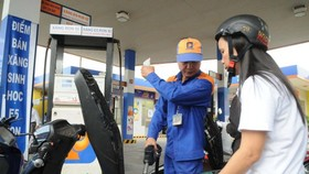 A customer fills gasoline E5 at a station in HCMC (Photo: SGGP)