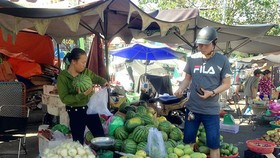 The man buys vegetables at a market in HCMC (Photo: SGGP)