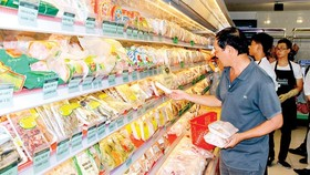 Customers choose products in the price stabilization program at San Ha Foodstore. (Photo: SGGP)