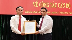 Head of the Commission for Organizing and Personnel of the Communist Party of Vietnam Pham Minh Chinh (R) gives the Politburo's decision to appoint Mr. Tran Luu Quang to the standing deputy secretary of HCMC Party Committee on February 27 (Photo: SGGP)