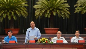 PM Nguyen Xuan Phuc (standing) at the meeting with highly-skilled workers in HCMC. (Photo: VNA)