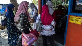 Dozens of people clutching bags full of plastic bottles and disposable cups queue at a busy bus terminal in the Indonesian city of Surabaya. (Photo: AFP)