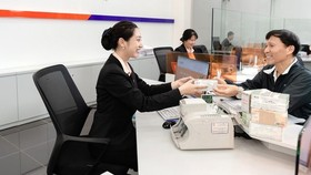 Customers receive remittances at a bank in HCMC (Photo: SGGP)