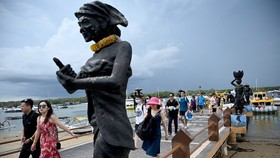 Chinese tourists, some wearing facemasks as a preventative measure following a coronavirus outbreak that began in the Chinese city of Wuhan, walk after arriving from Nusa Penida at the fast boat pier on Serangan Island in Denpasar, Bali(Source:AFP)