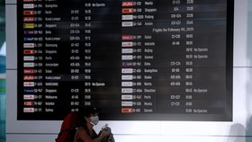 A passenger walks near the flight information board at the departure gate of I Gusti Ngurah Rai International Airport in Bali, Indonesia (Photo: Antara)