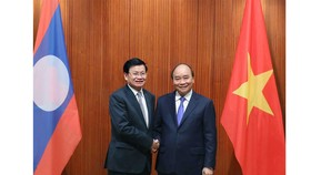 Prime Minister Nguyen Xuan Phuc meets with his Lao counterpart Thongloun Sisoulith during the Lao PM's visit to Vietnam on July 5. (Photo: VNA)