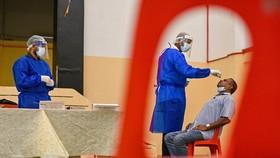 Medical workers take samples for COVID-19 testing in Kuala Lumpur, Malaysia, on January 18 (Photo: Xinhua/VNA)