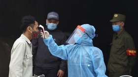 A man has his body temperature checked. (Photo: VNA)