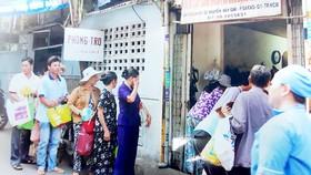 Người nhà bệnh nhân xếp hàng chờ nhận cơm của Bếp ăn từ thiện Bảo Hòa tại Bệnh viện Ung bướu TPHCM
