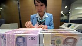 Kiểm tiền baht của Thái Lan tại ngân hàng Krung Thai ở Bangkok. Ảnh: AFP/TTXVN