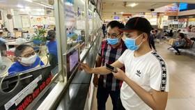 Hành khách khai báo y tế  tại Bến xe miền Đông chiều 27-3. Ảnh: CAO THĂNG