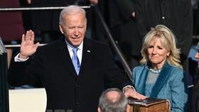 Ông Joe Biden (trái) tuyên thệ nhậm chức trước Chánh án Tòa án Tối cao John Roberts tại Đồi Capitol ở thủ đô Washington DC., ngày 20-1. Ảnh: AFP/TTXVN