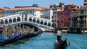 Khách du lịch đi thuyền gondola tại Venice, Italy. Ảnh: AFP/TTXVN
