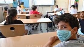 Học sinh đeo khẩu trang phòng lây nhiễm COVID-19 tại trường học ở châu Âu. Ảnh: AFP/TTXVN