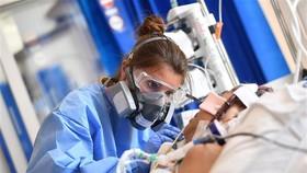 Nhân viên y tế điều trị cho bệnh nhân COVID-19 tại bệnh viện ở Cambridge, Anh. Ảnh: AFP/TTXVN