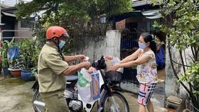 """Người dân """"vùng xanh"""" ở quận Tân Bình nhận quà tặng từ Công an quận Tân Bình. Ảnh: CAO THĂNG"""