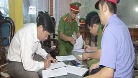Lê Hữu Lam ký vào các giấy tờ liên quan trước khi bị bắt