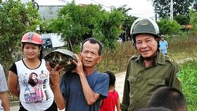Ông Thể và đại diện chính quyền địa phương cùng người dân mang con rùa đi thả về lại môi trường tự nhiên