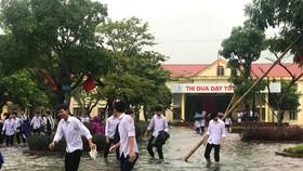 Nhiều em học sinh lội nước đến trường dự lễ khai giảng