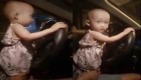Cháu bé với hai tay đang cầm vô lăng xe ô tô. Ảnh cắt từ clip