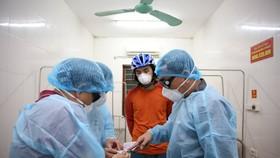 Bàn giao du khách Z. L. (áo đỏ) cho Bệnh viện Đa khoa Hà Tĩnh để tiến hành cách ly, theo dõi trong khi chờ kết quả xét nghiệm
