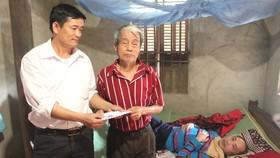 Đại diện UBND xã Đức Bồng, huyện Vũ Quang trao 12 triệu đồng của bạn đọc Báo SGGP cho gia đình anh Trần Sinh Nhật