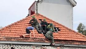 Lực lượng chức năng giúp người dân xã Thịnh Lộc, huyện Lộc Hà lợp lại mái nhà sau thiệt hại do lốc xoáy gây ra