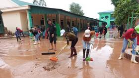 Các giáo viên cùng cán bộ công an hỗ trợ dọn vệ sinh môi trường tại Trường Mầm non Cẩm Mỹ
